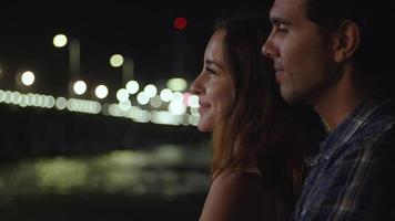 Cámara lenta de pareja joven alegre en la noche con luces de fondo