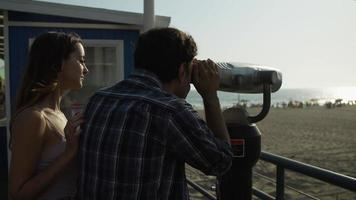 Slow motion of young couple using telescope on beach vacation