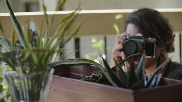 cámara lenta de joven fotografiando plantas