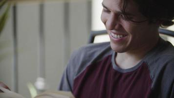 câmera lenta de jovem lendo livro sorrindo