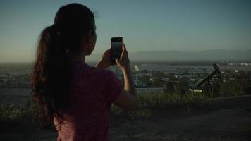câmera lenta de mulher fotografando cidade com telefone