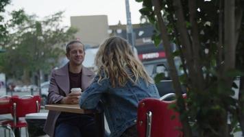 câmera lenta de casal tomando café na calçada da cafeteria