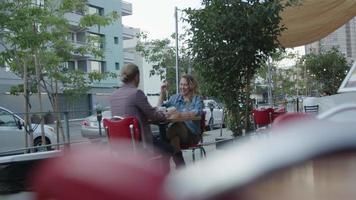 rallentatore delle coppie che bevono caffè nella caffetteria sul marciapiede video