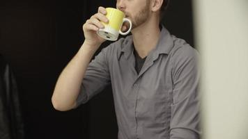 Zeitlupe des Mannes, der Kaffee zu Hause trinkt