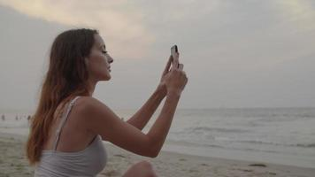 cámara lenta de mujer tomando fotos de playa