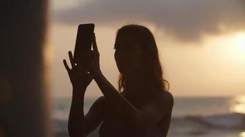 cámara lenta de mujer tomando fotos en la playa