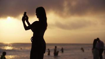 slow motion van vrouw die foto op strand