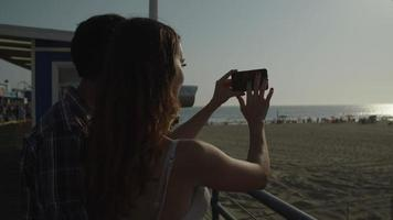 Slow motion of woman taking photo of beach with man