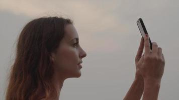 câmera lenta de mulher tirando foto no telefone video