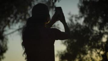 câmera lenta de mulher fotografando árvores com telefone