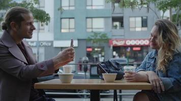 rallentatore di coppia in caffè all'aperto con uomo che cattura foto video