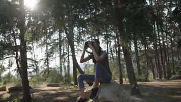 cámara lenta de mujer tomando fotos con cámara en el bosque