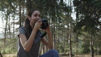 rallentatore della donna che cattura foto con la fotocamera nella foresta