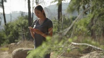 cámara lenta de mujer con smartphone en bosque