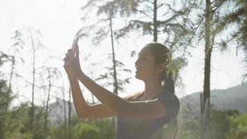 cámara lenta de mujer tomando fotos por teléfono en el bosque