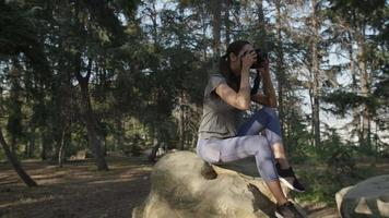 cámara lenta de mujer tomando fotos con cámara en el bosque video