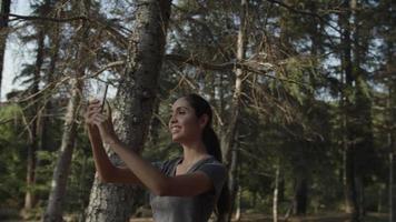 Cámara lenta de mujer tomando selfie por teléfono en el bosque