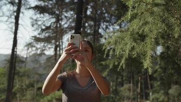 Cámara lenta de mujer tomando selfie por teléfono en el bosque video