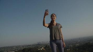 câmera lenta de mulher tirando selfie com o pano de fundo da cidade
