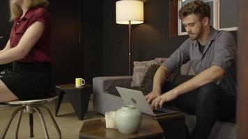 Slow motion of man using laptop on couch video