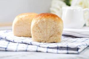 Pão fresco feito em casa no fundo da mesa branca