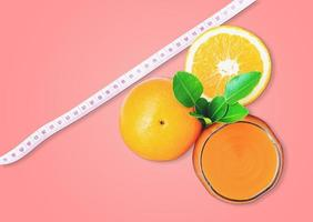Top view of orange juice and oranges with measuring tape