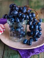 twig of blue grapes in a glass on a plate
