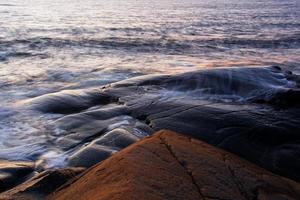 Rock formations and waves at seaside photo