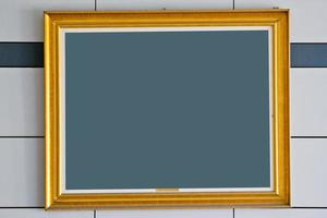 gold picture frame. Isolated over wall   background
