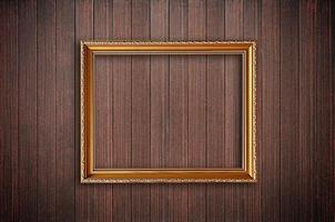 Golden picture frame on wooden wall photo