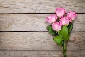 Fondo del día de San Valentín con rosas rosadas sobre mesa de madera foto