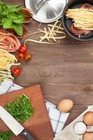 Ingredientes para cocinar pasta y utensilios de mesa de madera foto