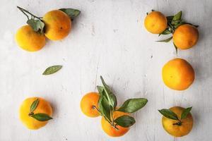 Frame of mandarins on the white wooden table horizontal