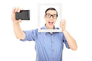 Man taking a selfie and holding picture frame photo