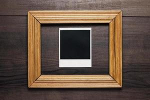 empty frame and old photo on wooden background