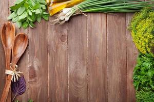 Fresh garden herbs on wooden table photo