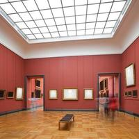 A distance shot of a museum gallery room with frames up