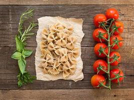 Pasta, tomatoes and herbs on wooden background