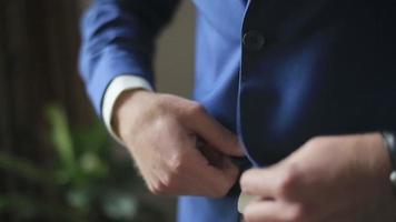 junger hübscher Mann im stilvollen blauen Anzug knöpft seinen Blazer zu