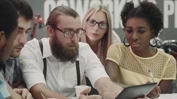 gruppo di collaboratori internazionali utilizzando tablet al tavolo