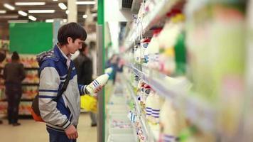 jovem escolhe e compra leite no supermercado. 1920 x 1080 video