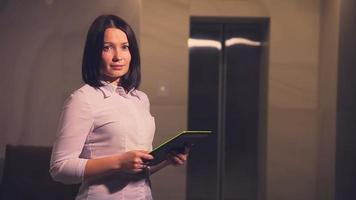 Young business woman hotel manager in an elevator with a Tablet PC video