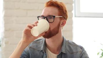 Mann, der einen Schluck Kaffee nimmt und im Büro sitzt video
