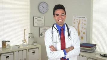Handsome mexican doctor standing in office