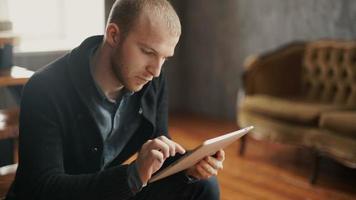 Porträt eines schönen jungen glücklichen Mannes unter Verwendung der digitalen Tablette
