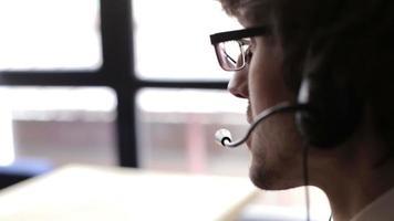 Retrato de operador de telefonía de soporte sonriente feliz en auriculares en el lugar de trabajo video
