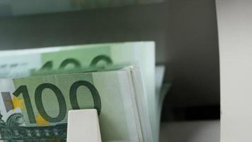 contadora de dinero en efectivo. El contador de billetes está contando billetes de cien euros. video