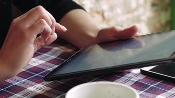 Woman hands touching tablet's display at a table with a cup of coffee video