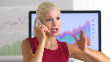 Business woman using cell phone in office video