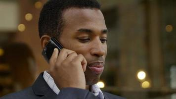 handsome black american/african businessman at work with cell phone